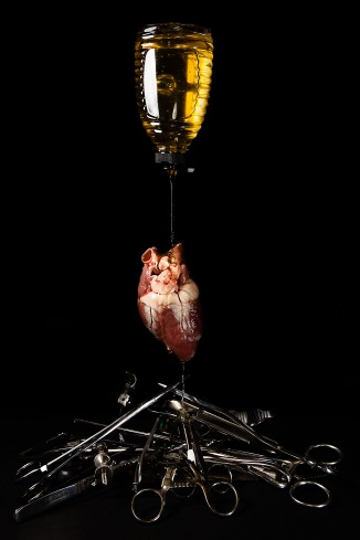 A pot of honey pours over a heart and onto a pile of surgical instruments
